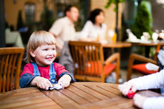 Little boy  playing and smiling. Little boyl playing on table with toy cars parents in background defocused Royalty Free Stock Images