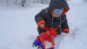 Little boy playing with snow stock video
