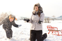 Little boy playing in the snow with Mother Royalty Free Stock Image
