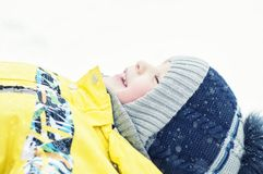Little boy playing in the snow, portrait, lying on his back, laughing royalty free stock photography