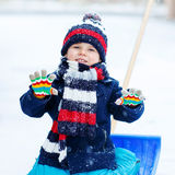 Little boy playing with snow in winter, outdoors. Royalty Free Stock Photos
