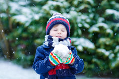 Little boy playing with snow in winter, outdoors. Royalty Free Stock Images