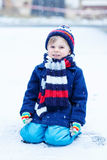 Little boy playing with snow in winter, outdoors. Stock Image
