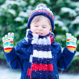 Little boy playing with snow in winter, outdoors. Stock Photos