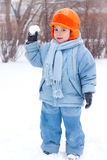 Little boy playing snowballs Stock Images