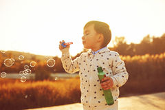 Little boy playing with soap bubbles Stock Photo