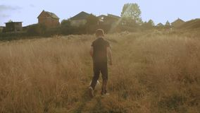 Little boy playing soccer in the field. Child running through meadow with a ball. Countryside and forest
