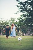 Little boy playing soccer football with mother
