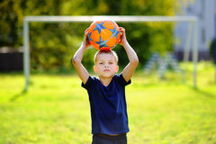 Little boy playing a soccer game on summer day stock photo