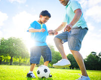 Little Boy Playing Soccer With His Father Stock Photo