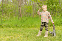 Little boy playing at soldiers standing saluting Royalty Free Stock Image