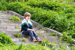 Little boy playing on the stairs on a garden Stock Photos
