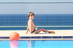 Little boy playing at the swimming pool Stock Image