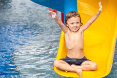 Little boy playing in the swimming pool on slide Stock Images