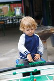 Little boy playing table soccer and football outdoors Stock Image