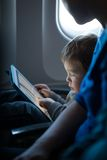 Little boy playing with a tablet in an airplane. Little boy sitting in his seat during a flight playing contentedly with a tablet computer in an airplane watched Royalty Free Stock Images
