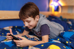 Little boy playing on tablet at home Stock Image