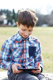 Little boy playing on tablet outdoor Stock Image
