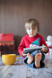Little boy, playing on tablet. Sitting on the floor with a big mug Royalty Free Stock Photos