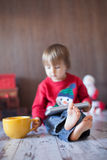 Little boy, playing on tablet. Sitting on the floor with a big mug Stock Photography
