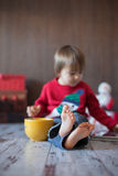 Little boy, playing on tablet. Sitting on the floor with a big mug Stock Photo