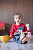 Little boy, playing on tablet. Sitting on the floor with a big mug Stock Image