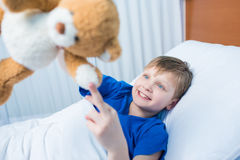 Little boy playing with teddy bear while lying in hospital bed stock photos