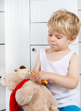 Little boy playing with teddy bear toy and brushing teeth. Stock Photos
