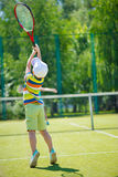 Little boy playing tennis. Little cute boy playing tennis on green court Royalty Free Stock Image