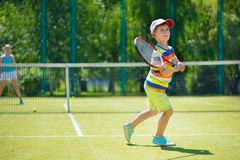 Little boy playing tennis. Little cute boy playing tennis on green court Royalty Free Stock Photo