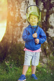 Little boy playing tennis at park. Little boy playing tennis in the forest Stock Photos
