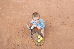 Little boy playing with a tennis racket and ball at tennis court. View from above.  Royalty Free Stock Photo