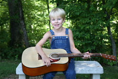 Little boy playing theguitar. Cute boy in overalls sits on a bench playing the guitar Stock Photo