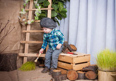 Little boy is playing with the tools of a carpenter. Stock Photos