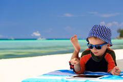 Little boy playing on touch pad at beach Royalty Free Stock Image