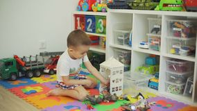 Little boy playing with toy animals at home. Little boy putting toy animals into a toy house. He is playing on the floor in nursery room stock video
