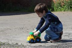 Little boy playing with a toy car Stock Image