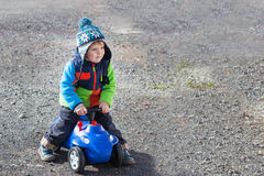 Little boy playing with toy car, outdoors Stock Image