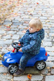 Little boy playing with toy car, outdoors Royalty Free Stock Photo