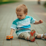 Little boy playing with toy car Stock Image