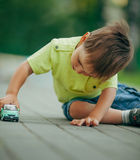 Little boy playing with toy car royalty free stock photos