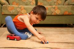 Little boy playing toy cars on the floor Royalty Free Stock Photos