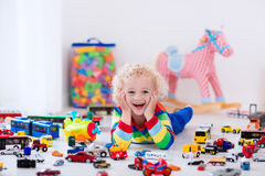 Little boy playing with toy cars Stock Photos