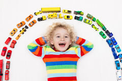 Little boy playing with toy cars. Toys for kids. Stock Photos