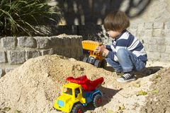 Little boy playing with toy digger and dumper truck. Little three year old boy playing in the sand with a digger and dump truck Royalty Free Stock Photos