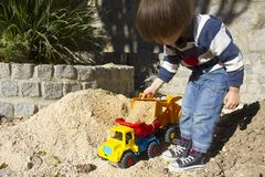 Little boy playing with toy digger and dumper truck. Little three year old boy playing in the sand with a digger and dump truck Royalty Free Stock Photo