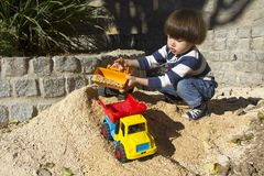 Little boy playing with toy digger and dumper truck. Little three year old boy playing in the sand with a digger and dump truck Stock Image