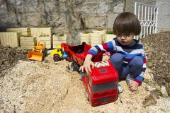 Little boy playing with toy digger and dumper truck. Little three year old boy playing in the sand with a digger and dump truck Stock Photo