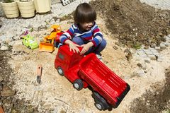 Little boy playing with toy digger and dumper truck. Little three year old boy playing in the sand with a digger and dump truck Royalty Free Stock Images