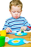 Little boy playing with toy kitchen Royalty Free Stock Photos